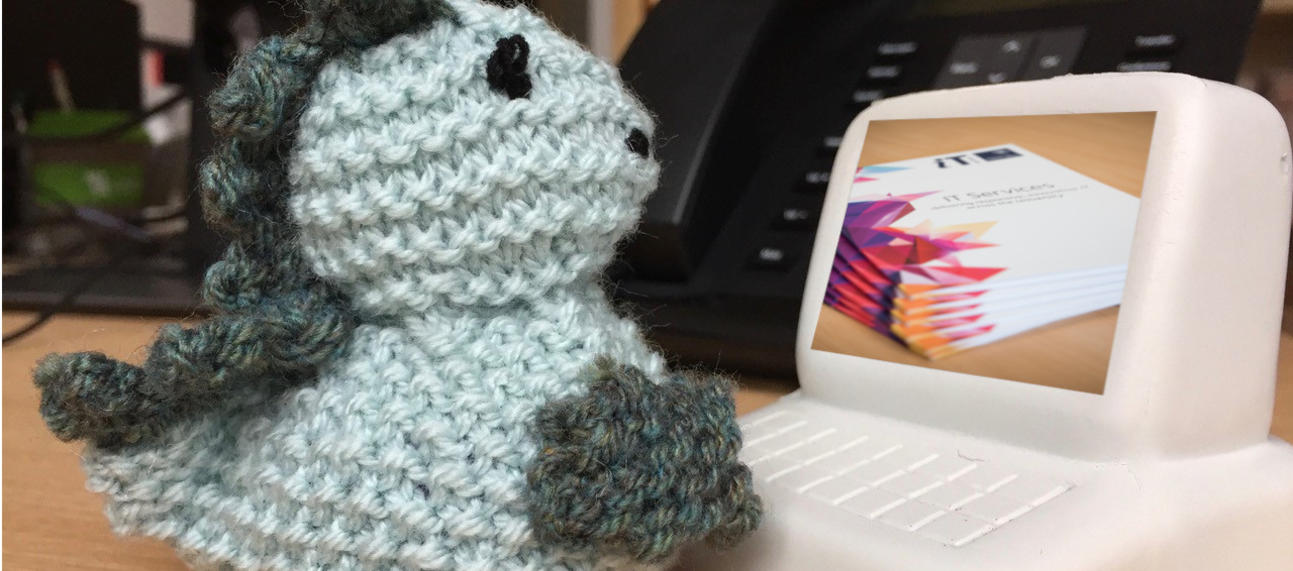 Knitted toy typing on toy computer - IT Services branding on screen