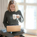 woman with laptop drinking coffee