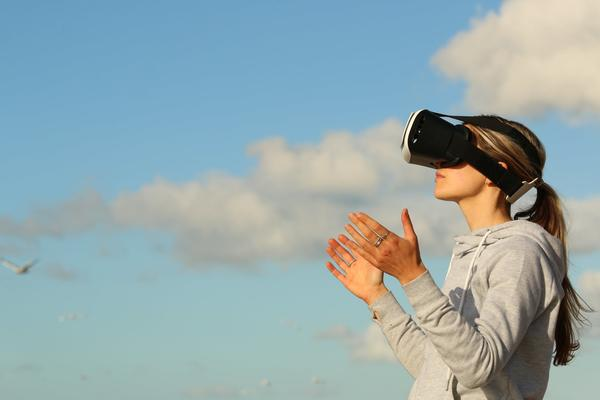 Girl wearing VR goggles looking at sky