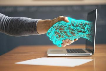 Digital hand emerging from a laptop monitor and shaking hands with a person