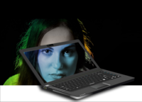 Laptop with person behind it but their face showing on the screen